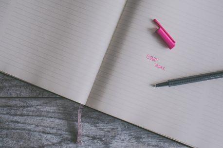"Capitalized text ""start today"" written in black pen on black line notebook."