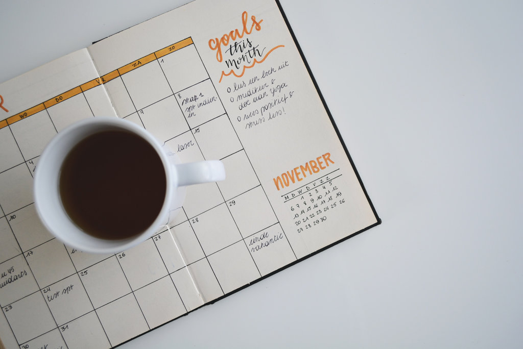 "White ceramic coffee mug on top of a planner titled ""goals this month""."