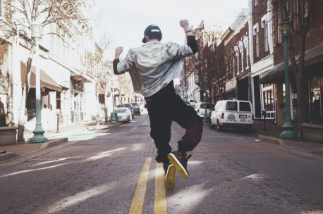 Man jumping in celebration on the middle of the street during daytime.