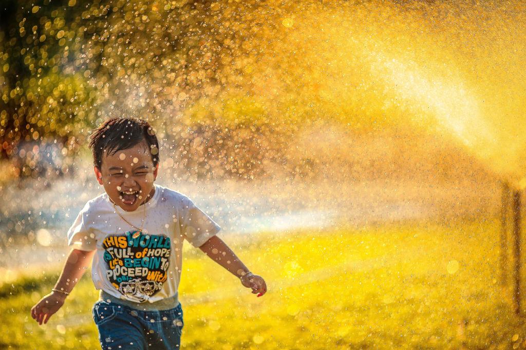 A boy joyfully running through sprinklers.