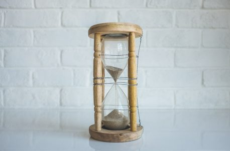A flowing hourglass with sand almost completely in the lower bulb.