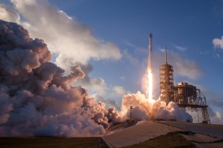 Spacecraft taking off in a blaze of smoke and fire.