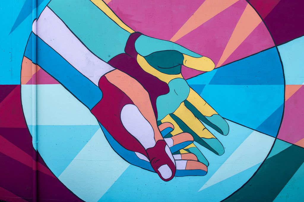 A painting depicting a pair of colorful hands.