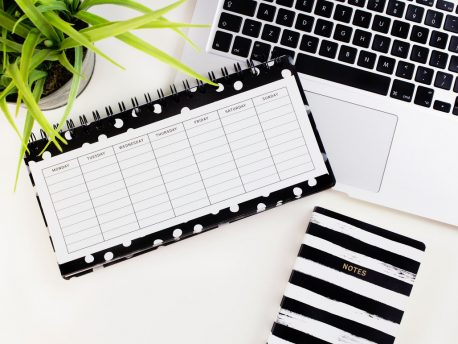 An empty weekly planner on a white desk partly covering a laptop keyboard.