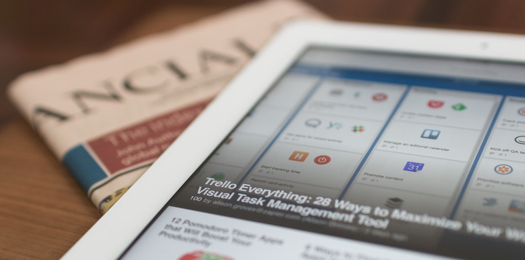 A tablet with an open article on top of a newspaper.