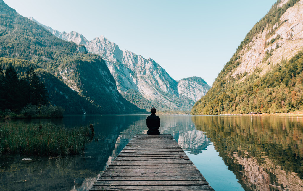A person sitting on a dock of a beautiful lake surrounded by mesmerizing mountains.