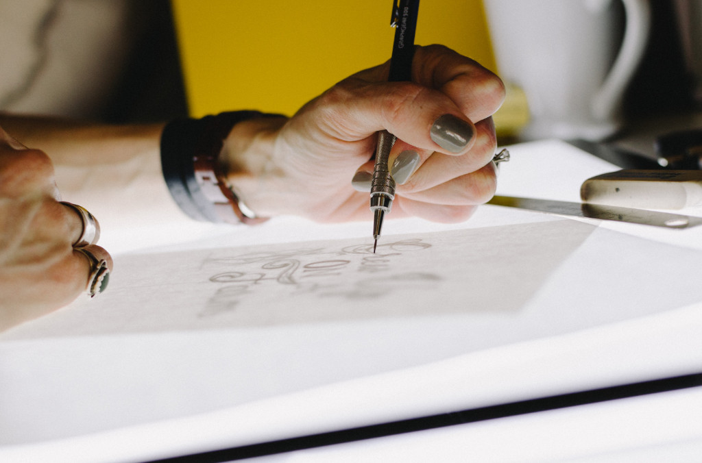 A person at a bright table drawing using a mechanical pencil.