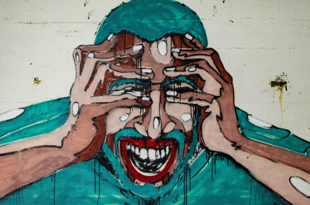 An abstract painting of a man holding his eyes and screaming.