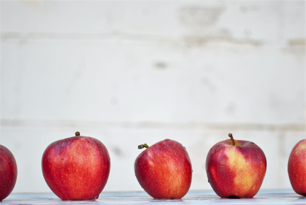 Five oddly shaped red apples on a white surface.