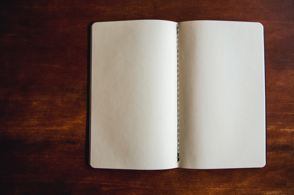 An open blank notebook on a desk.