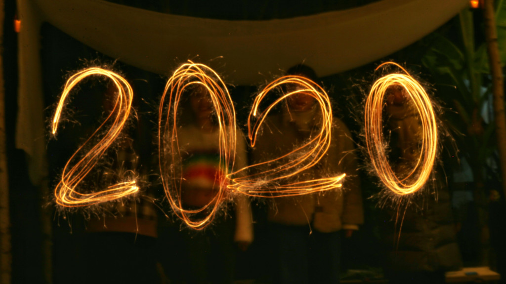 2020 written in light with people standing in the background.