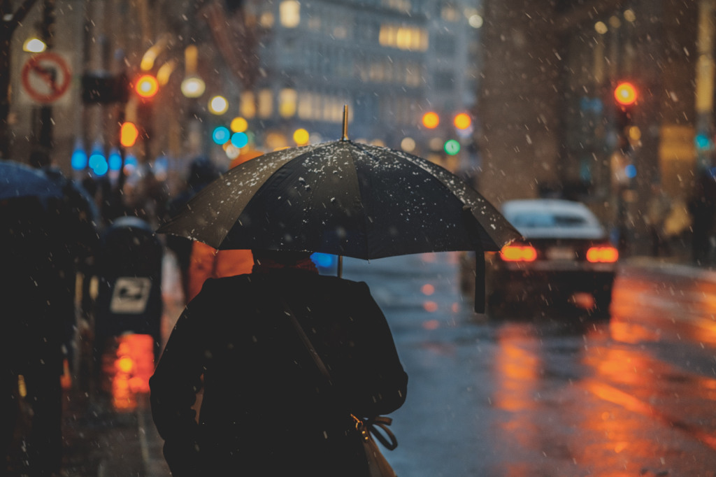 A person walking on a street in the rain, holding an umbrella.