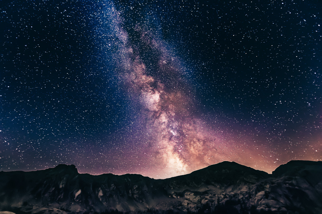 A night sky full of stars with a Milky Way galaxy in the center, behind mountains.