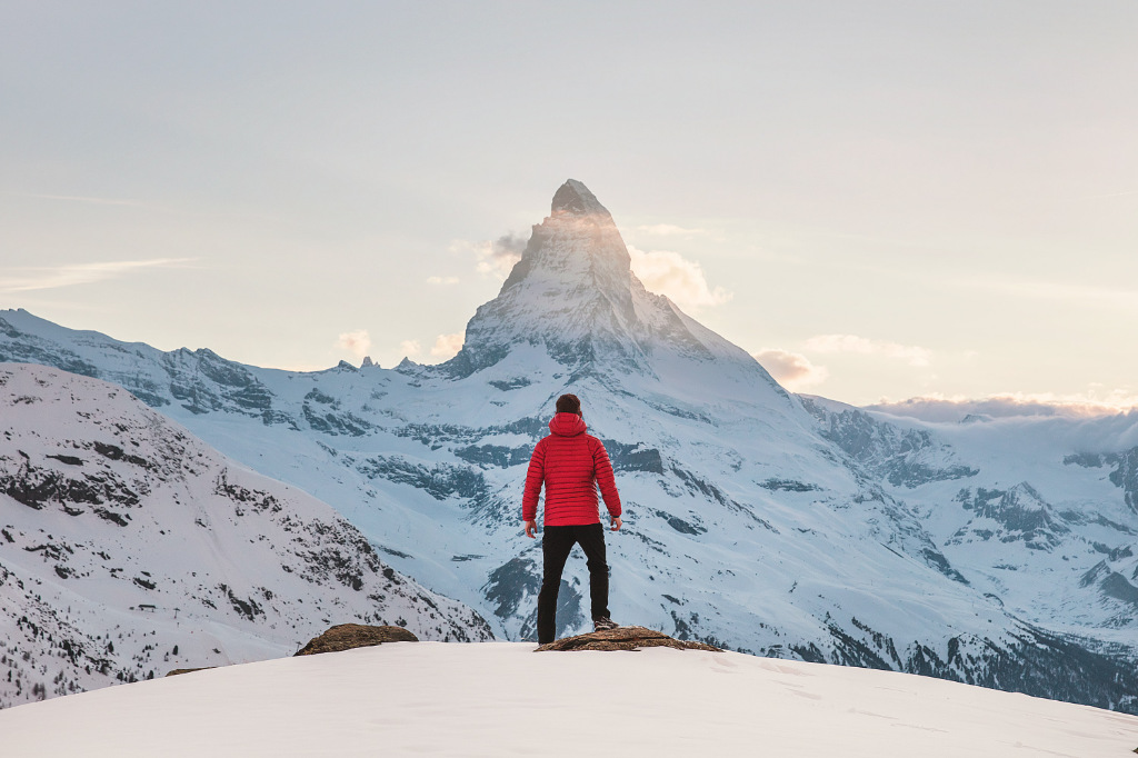 A person in a red hoodie standing on snow, looking at a distant mountain top.