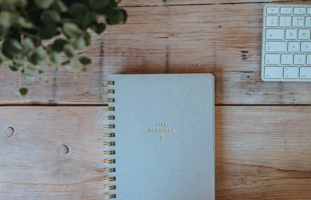 "Gray notebook on a desk labeled ""Life Planner""."
