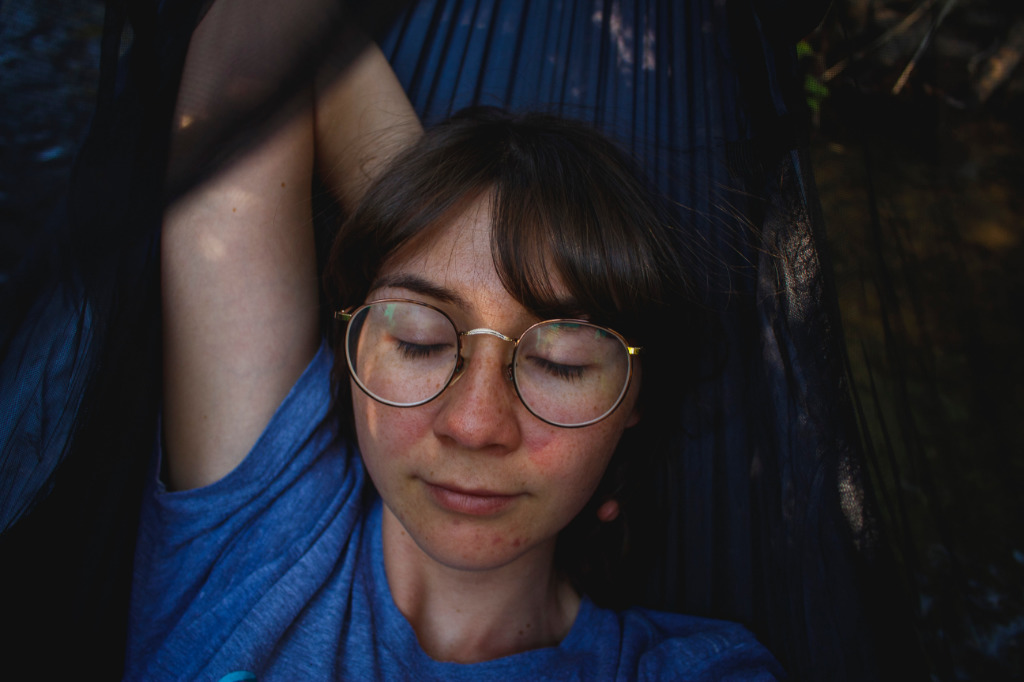 A woman in a blue t-shirt resting in a hammock.