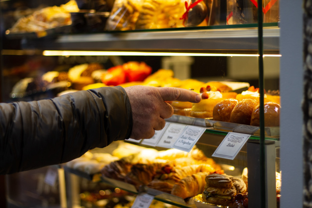 A person pointing to a wide selection of sweet pastries.