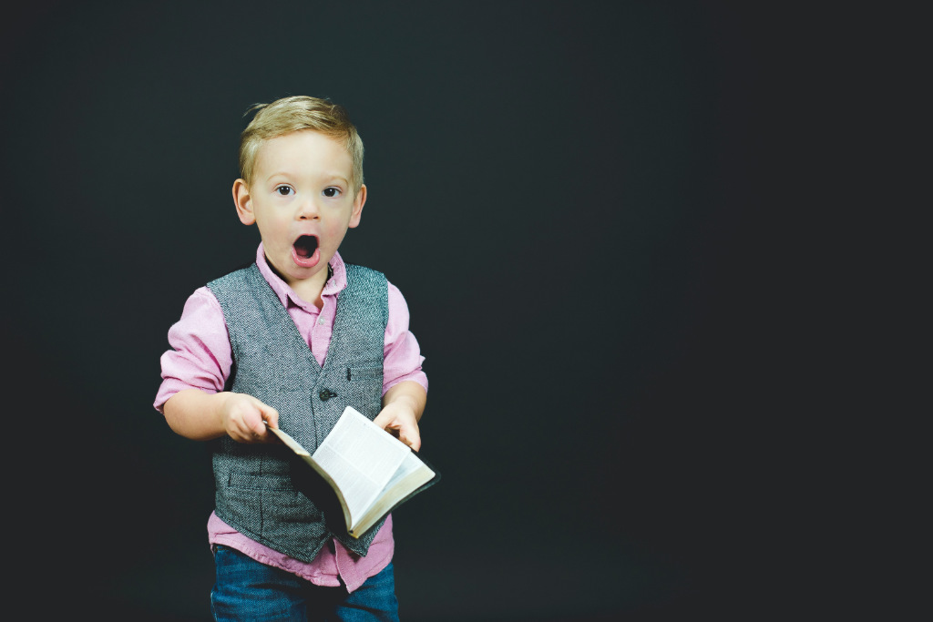 A boy holding a book with a surprised look on his face.